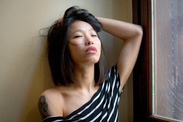 Beautiful sensual asian woman posing thoughtful at window