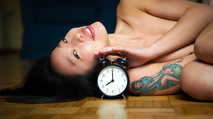 Woman lying and smiling on wooden floor with alarm clock