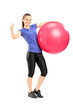 Woman holding an exercise ball and giving a thumb up