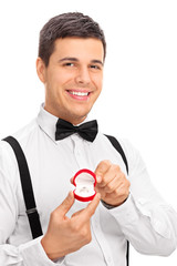 Elegant young man holding an engagement ring