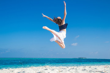 Young girl jumping at tropical beach