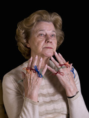 Old woman, with strings attached in the fingers