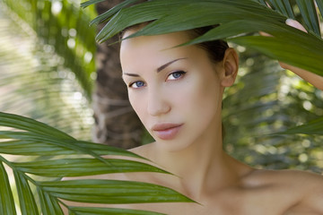 Beautiful woman hiding behind the palm leaves