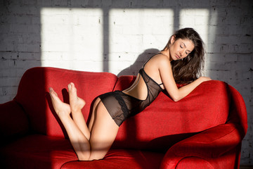 Beautiful girl in black peignoir posing on red sofa