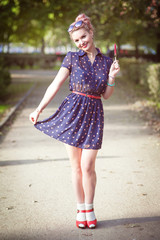 Beautiful young woman in fifties style with braces holding candy