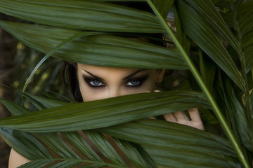 Sexy beautiful woman hiding behind the palm leaves. Beautiful st
