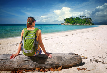 Woman with backpack relaxing on coast and looking to a island