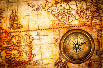 Vintage compass lies on an ancient world map.