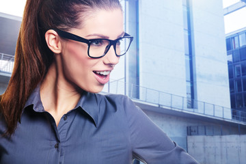Business woman with glasses on office building background
