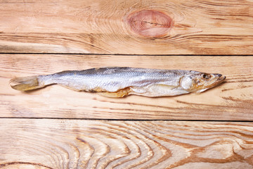 Dried salted fish on a wooden background