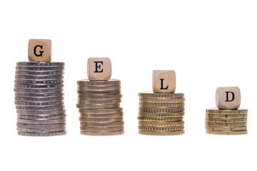 Geldstapel und Holzwürfel mit dem Wort Geld