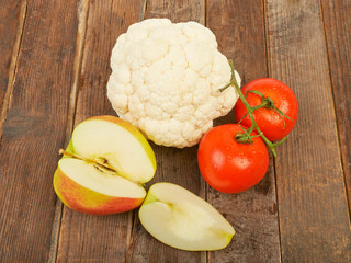 Cauliflower, apples and tomatoes, some salad on the table wooden