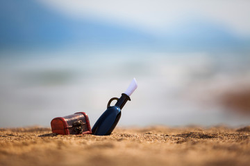 Bottle and chest on a beach