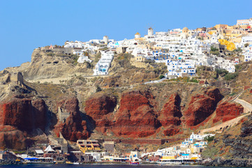Oia and red volcanic cliff rocks of Santorini island