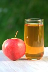 szklanka soku jabłkowego i jabłko na stole w ogrodzie