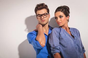 fashion couple posing on grey studio background.