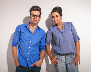 Young man and woman leaning on a grey wall