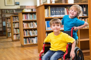 Cute pupils smiling at camera at the library