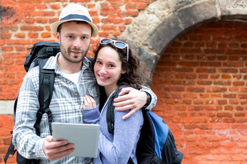 Young couple of tourists using tablet to visit city
