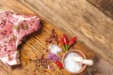 Fresh meat steak with spices on a wooden rustic table