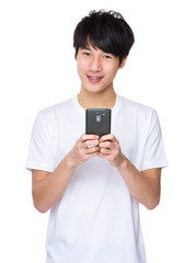 Young asian man texting message at his mobile phone