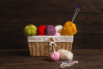 Wool yarn in coils with needles in wicker basket