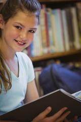 Little girl reading on library floor