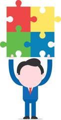 Businessman lifting puzzle pieces