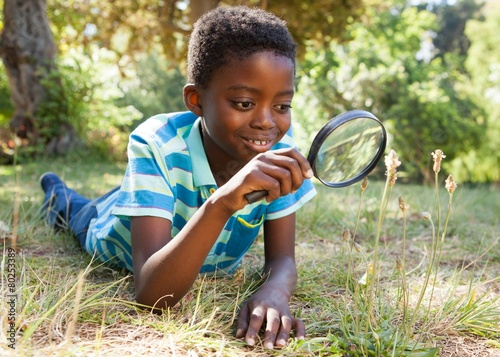 Cute little boy looking through magnifying glass - 80253389
