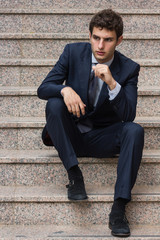 Young businessman sitting on stairs