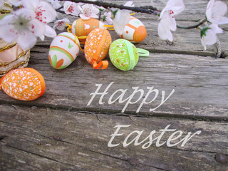Easter card with eggs and flowers on wooden background