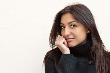 Портрет красивой молодой темноволосой женщины на фоне стены