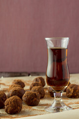 Small glass of brandy and homemade candies wooden table
