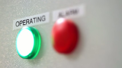 Green operating and red alarm buttons on industrial equipment