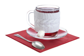 glass cup with red tea in a white sweater
