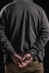 Arested man in handcuffs from back