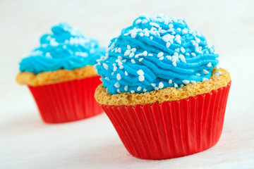 Two cupcakes with blue icing and coarse sugar
