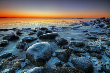 Frosted beach and rocks with colorful sunrise