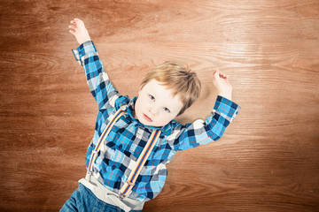 little boy on wooden floor