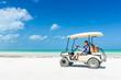 Young woman driving golf cart along tropical sandy beach - 80262357
