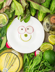 White plate with a smile of spring ingredients surrounded