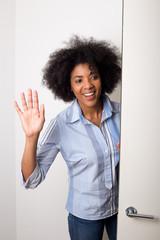 a young woman waving goodbye at the door