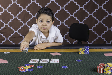 A young boy playing poker at a table