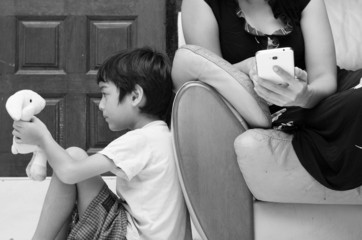 Little boy sitting and playing alone while mother busy on social