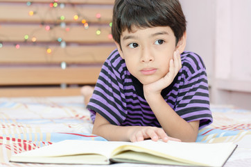 Little boy thinking while writing in the room