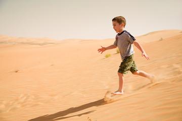 Young boy runs down in desert sand