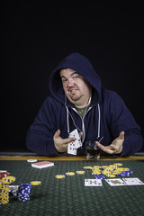 A man playing poker sitting at a table bluffing