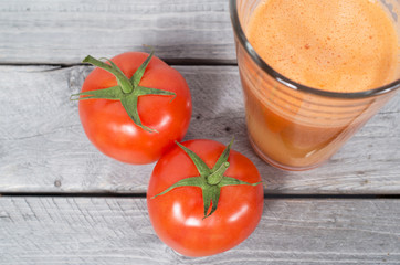 Fresh tomato juice with whole vegetables iagainst wooden backgro