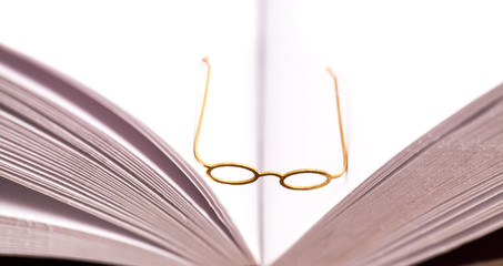 Small reading glasses on open book