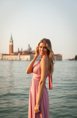 Beautiful girl in pink dress in Venice